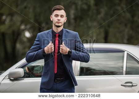 Successful business man in a dark business suit with a red tie against the background of a car. Stylish business man in a dark suit. Business professions. Business concept. Business vision. Successful business man in a classic suit