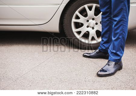 Footwear concept. Footwear for outdoor activities. Classic footwear. A man in black elegant footwear against the background of the car. Stylish clothes