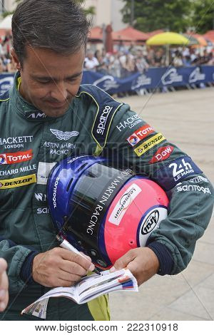 LE MANS, FRANCE - JUNE 11, 2017: Portuguese race car driver Pedro Lamy Aston Martin Racing in the uniform gives autograph during parade of pilots racing at Le mans, France
