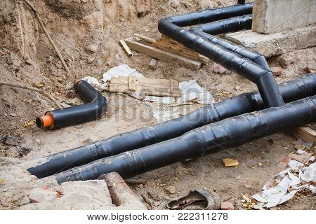 Water pipes with insulation lie on the grass. Water pipes industry. Heavy industry. The industry of pipes. Metal industry
