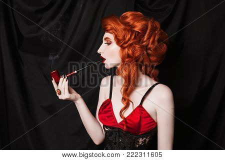A red-haired woman in a black corset smoke a pipe on a black background. Conceptual photography with pipe for for smoke. Young woman smoke in underwear. Conceptual picture of a girl who smokeConceptual photography