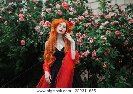 Red-haired girl with pale skin in a black summer dress with a red cape on her shoulders against summer background of a bush of pink summer roses. A model on a summer background. Beautiful summer flowers. Summer time