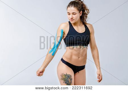 Concept of sports medicine and health. beautiful girl with good figure posing on gray background with kinesiology tape, a sticky blue ribbon on her arm.Alternative medicine for stretching and pain.