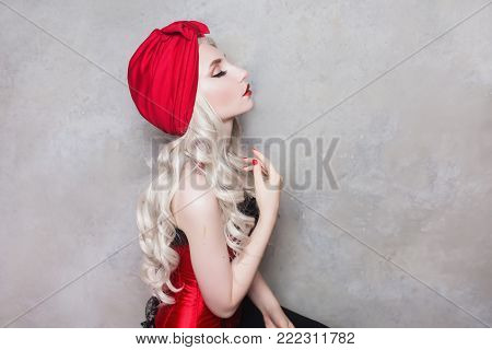 Glamour woman with pale skin and a high glamour hairdo with beautiful precious glamour ornaments from white beads. Beautiful glamour girl with red lips. Glamour model. Glamour make up