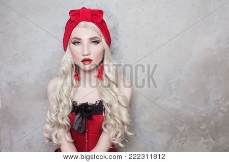 Interesting photo with people. Conceptual photography with people. An unusual image of people. Young people in the picture. Luxurious blonde woman with beautiful long white hair and red lips in a red turban on a gray background.