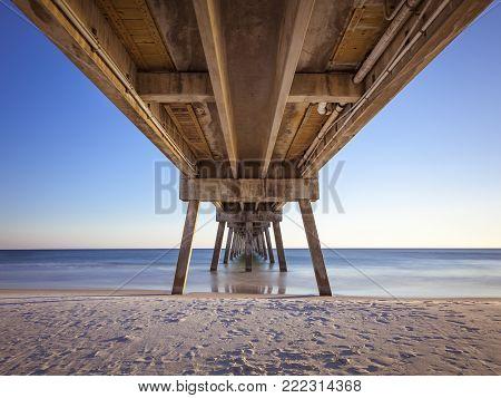 Okaloosa fishing pier in Fort Walton Beach, Florida on a sunny afternoon. Blur motion of birds in flight.