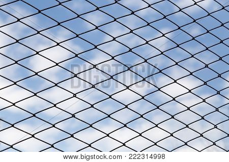 metal fence against the blue sky with clouds .