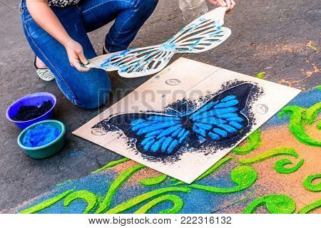 Antigua, Guatemala -  April 14, 2017: Decorating dyed sawdust Good Friday procession carpet with butterfly detail in town with most famous Holy Week celebrations in Latin America