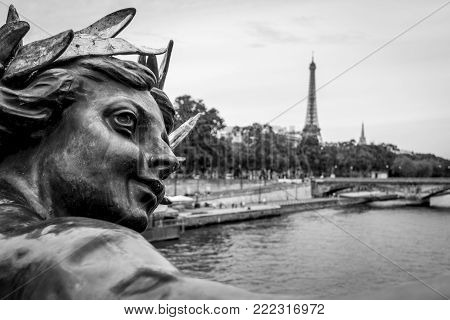 View to Seine river and big metallic man statue decorated on Pont Alexandre III in Paris