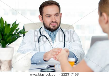 Doctor and patient. Hand of doctor reassuring her female patient