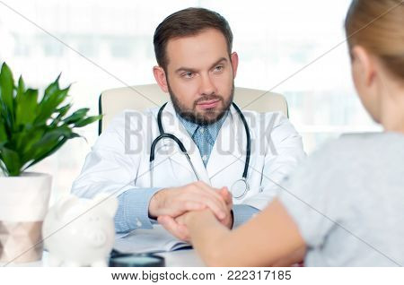 Doctor and patient. Doctor looking at his woman patient while speaking to her