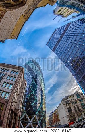LONDON, ENGLAND - NOVEMBER 27, 2017: Fish eye view with the famous Gherkin Tower (30 St Mary Axe) between old and new buildings.