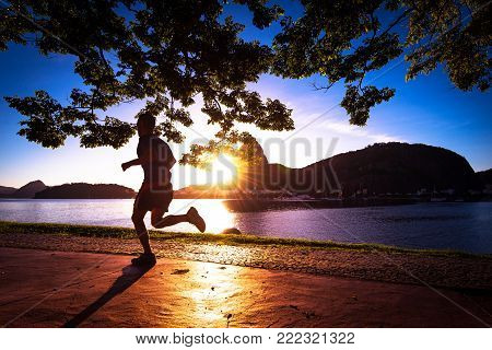 Silhouette of Man Running in the Early Morning during Beautiful Warm Sunrise in Rio de Janeiro with Sugarloaf Mountain in the Horizon