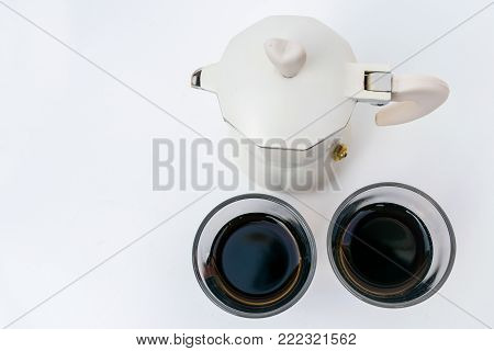 espresso coffemaker with hearth shaped holder and two glass cups of coffee on white background