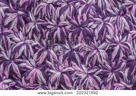 Texture of the knitted fabric. Crochet from yarn, handmade. A pattern asterisks or snowflakes of color yarn.