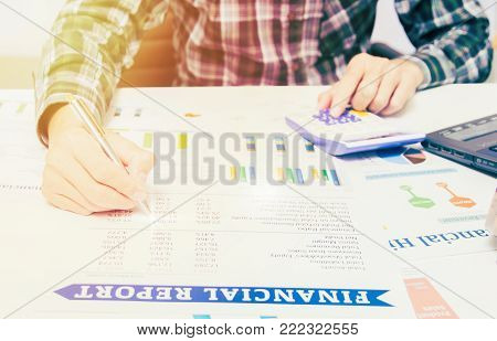 business finance accounting concept: business man hand using calculator and finance sheet report analysis on office desk.