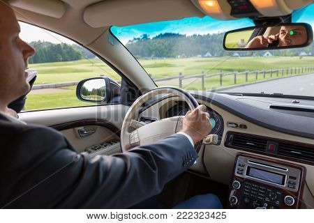 Businessman talking on cell phone while driving not paying attention to the road. Focus on the man face in rearview mirror.