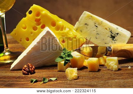 Several varieties of cheeses close-up on old wooden board with cheese knife and oregano