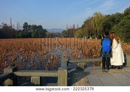 HANGZHOU, CHINA-JAN 08, 2018: A couple visit West Lake in Hangzhou, China during winter