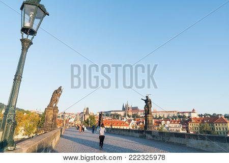 PRAGUE CZECH REPUBLIC - AUGUST 29,2017; Charles Bridge before sunrise tourists walking across under staute of St John Baptist pointing way.