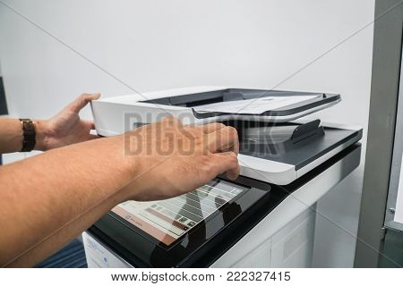 close up businessman press on office printer for copying and scanning documents