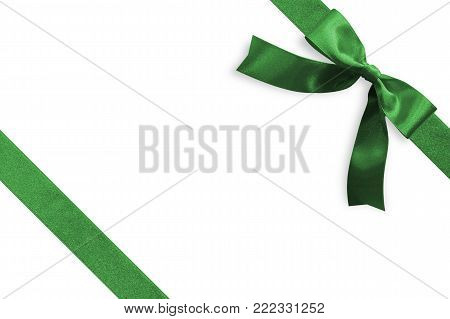 Green bow satin ribbon band stripe fabric emerald jade color on corner (isolated on white background with clipping path) for Christmas holiday gift box present wrap design decoration ornament element