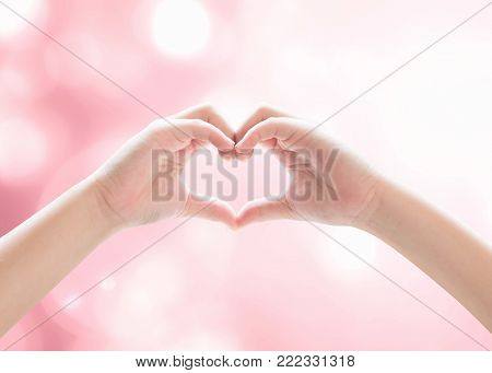 Heart-shape hand gesture of kid's body language for children's love, peace, kindness and world humanitarian aid concept. (Hand isolated on sky background with pink bokeh and sun flare)