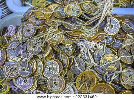 Old Chinese Copper Qing Dynasty Money Coins Panjuan Flea Market Beijing China.  Panjuan Flea Curio market has many fakes, replicas and copies of older Chinese products, many ancient. Chinese would tie money together to hide it before there were banks.
