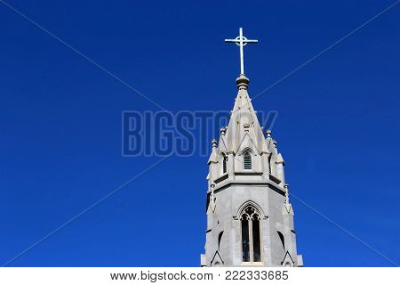 Crucifix on tall catholic church steeple with blue sky copy space St Augustine, Culver City, California.