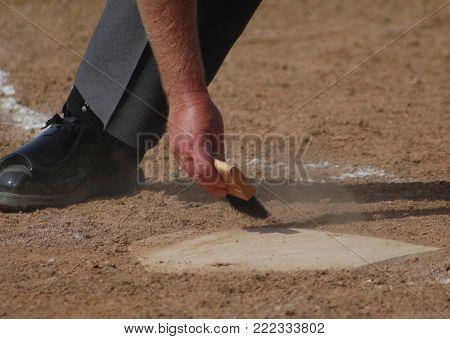 Baseball Umpire Wiping Home Plate Clean Restart