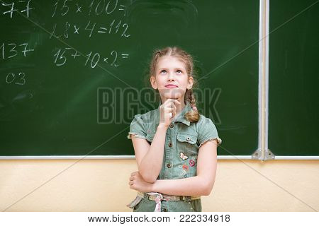Schoolgirl in the classroom standing at the blackboard solves an mathematic example