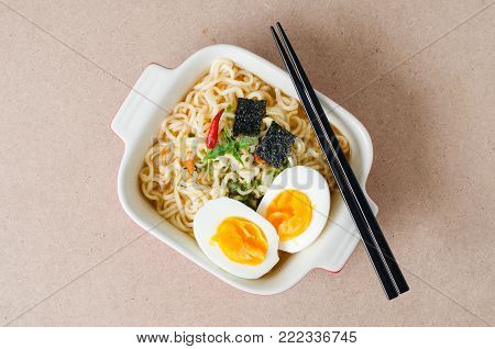 Instant noodles with boiled egg and seaweed in a bowl