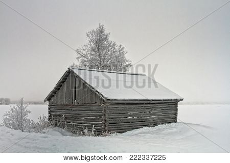 Old Barn With Wide Doors By The Snowy Field
