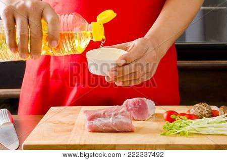 Chef's hand pouring oil in to a bowl and mix with raw pork and vegetables for roast pork cooking