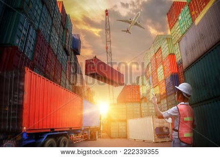 Female dock worker control, Forklift handling container box loading and Container Cargo freight ship with working crane bridge in shipyard at sunrise for Logistic Import Export background
