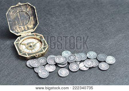 A toy compass with old pirate coins for a pirate game