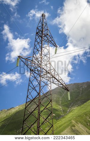 A power transmission mast close-up in a mountainous area.