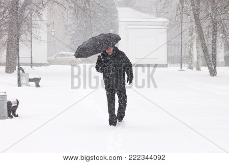 Very bad weather in a city in winter: terrible heavy snowfall and blizzard. Male pedestrian hiding from the snow under umbrella outdoors