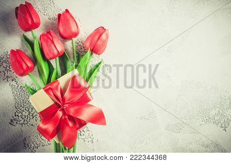 Bouquet of red tulips and gift box on white background. Spring flowers. Spring background. Greeting card for Valentine's Day, Woman's Day and Mother's Day. Top view, copy space.