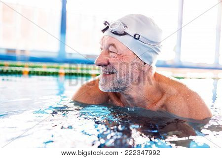Senior man in an indoor swimming pool. Active pensioner enjoying sport.