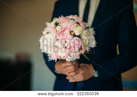 The courageous groom dresses his wedding suit. He holds a bouquet in his hands. Wedding day.