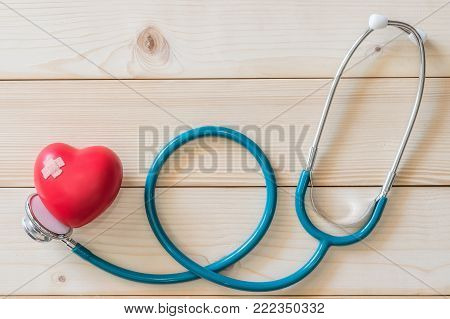 World health day campaign with red love heart  with cross bandage and medical doctor's stethoscope, first aid concept