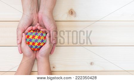 World Autism Awareness day concept with puzzle or jigsaw pattern on heart with autistic child's hands supported by nursing family caregiver