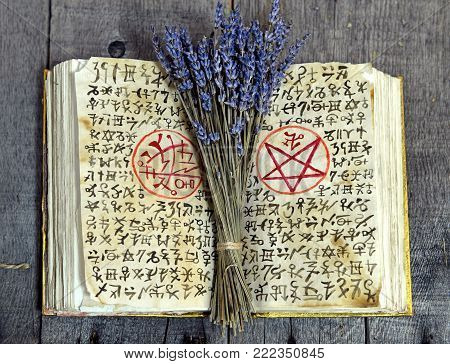 Old book with black magic symbols and lavender bunch on witch table. Occult, esoteric, divination and wicca concept. No foreign text, all symbols on pages are fantasy, imaginary ones