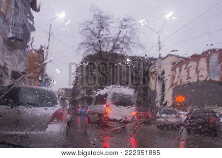 rain on the city street through a car windshield. Rain drops on window, rainy weather. inside car when rainning