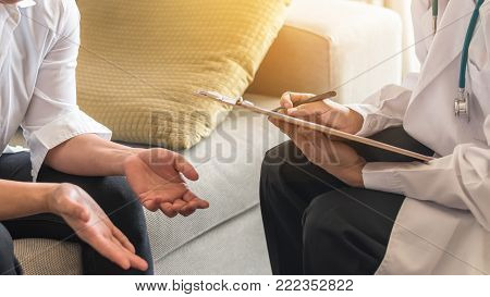 Psychiatrist or medical doctor (gynecologist) consulting and diagnostic examining woman patient's health in clinic office or hospital health service center