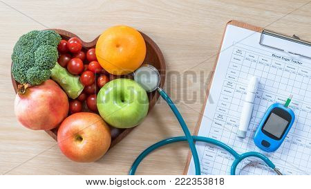 Diabetes monitor, Cholesterol diet and healthy food eating nutritional concept with clean fruits in nutritionist's heart dish and patient's  blood sugar control record with diabetic measuring tool kit