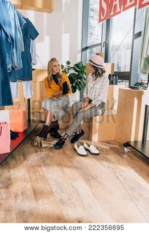 young shopping buddies choosing boots in clothing store