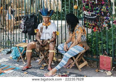 Belo Horizonte, Brazil - Dec 24: 2017: Brazilian indigenous Tupi and Tapuia man dressed in a traditional costume looks at cell phone