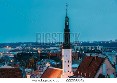 Tallinn, Estonia. Tower Of Church Of Holy Ghost Or Holy Spirit In Winter Evening Night. UNESCO Heritage Site. Night Cityscape. Destination Scenic